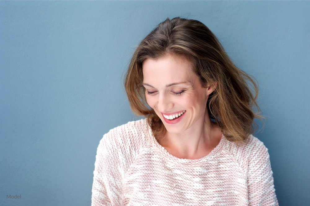 Happy, middle-afed woman with smooth facial skin that would be possible with a facelift.